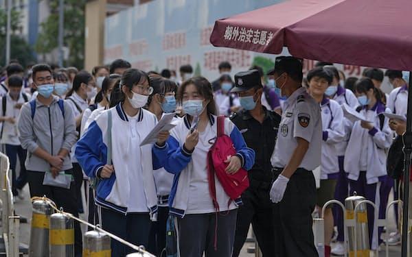 中国の受験競争も激しく親の教育熱は高い(北京市で全国統一大学入試「高考」にのぞむ受験生、6月7日)=AP