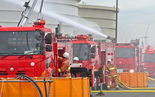 首都直下地震を想定した防災訓練で、石油タンクに放水する消防隊員(1日午前、川崎市川崎区)