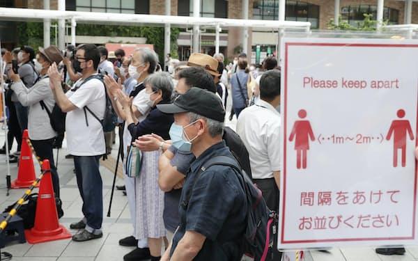 間隔を空けるよう呼びかける看板が掲げられる中、街頭演説を聞く有権者ら(25日午前、東京都武蔵野市)