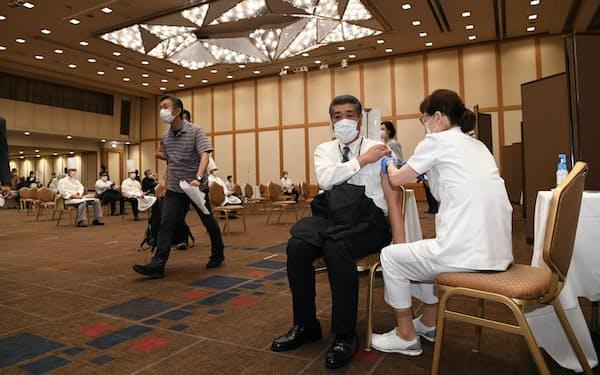 新型コロナウイルスワクチンの接種を受ける帝国ホテルの従業員(右から2人目)=21日午後、東京都千代田区、今村幸祐撮影