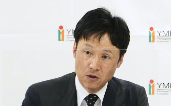 記者会見する山口FGの椋梨敬介社長(25日、山口県下関市)