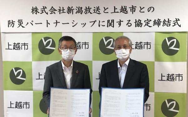 協定書に署名し、記念撮影する佐藤社長㊧と村山市長(28日、上越市役所)