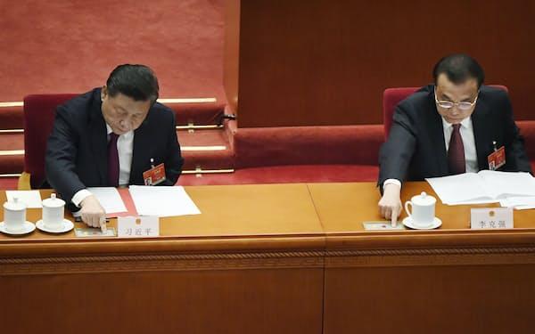 中国全人代で、香港の選挙制度見直しに関する決定案について投票する習近平国家主席(左)と李克強首相=11日、北京の人民大会堂(共同)
