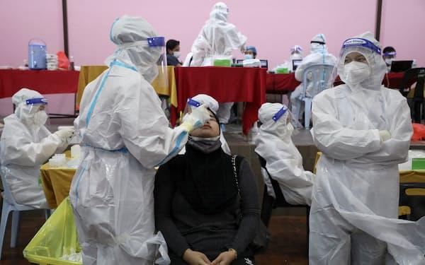 新型コロナ感染者の高止まりで、6月1日に始まったロックダウン(都市封鎖)は間もなく2カ月目に入る(写真はクアラルンプール近郊の検査会場)=ロイター