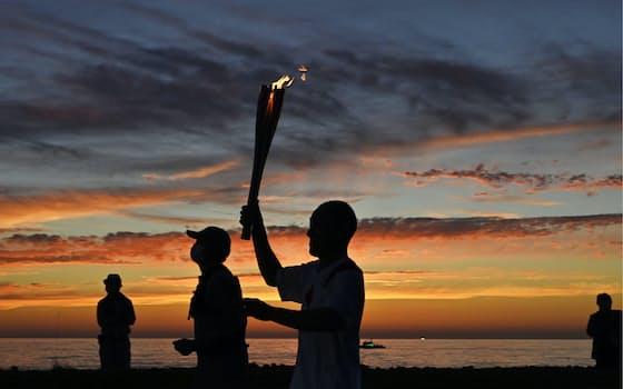 沈む夕日に照らされた日本海沿いを走る聖火ランナー(6月5日、新潟県村上市)=共同