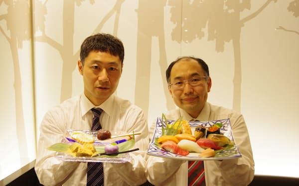 東鮓本店の横井健太郎専務㊨と和菓子を手に取る不朽園の杉村武宏社長