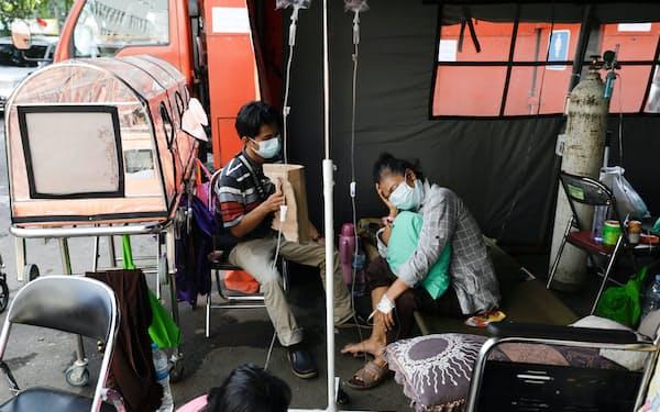 インドネシアでは新型コロナウイルス感染者の急増に対応するため屋外のテントで処置する病院も出始めた(6月25日、ジャカルタ近郊)=ロイター