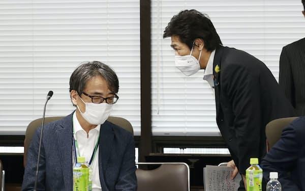 新型コロナウイルス対策を助言する専門家組織の会合に臨む田村厚労相。左は座長の脇田隆字・国立感染症研究所長(30日午後、厚労省)=共同