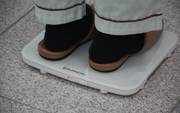 体重計のように患者が機器の上に乗って測定する