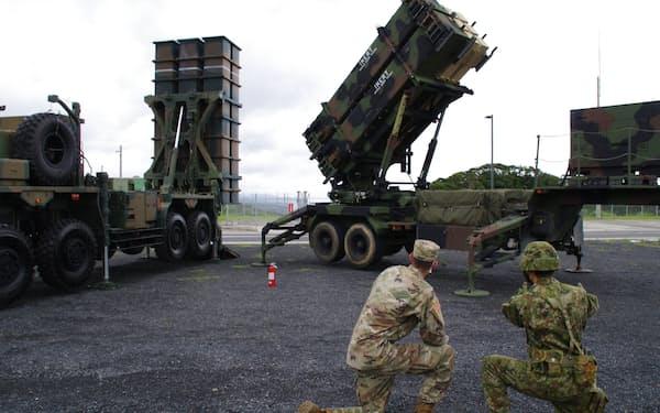 共同訓練する自衛官と米兵士。奥は米陸軍のPAC3㊨と陸自の地対空誘導弾(1日、鹿児島県奄美市)