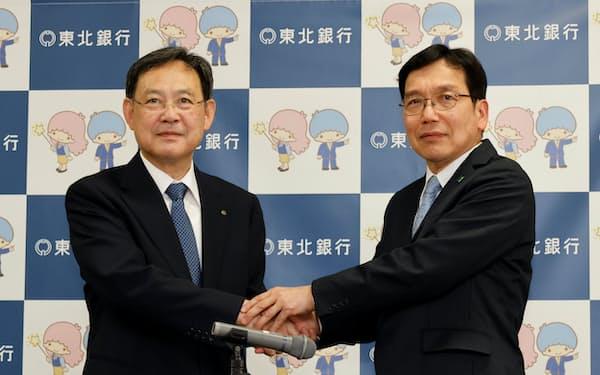 記者会見後に握手する東北銀の村上頭取(左)とフィデアHDの田尾社長(2日、盛岡市)