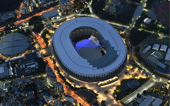 夕闇に包まれる東京五輪メインスタジアムの国立競技場。場内では青い光が照射されていた(6月9日)=共同