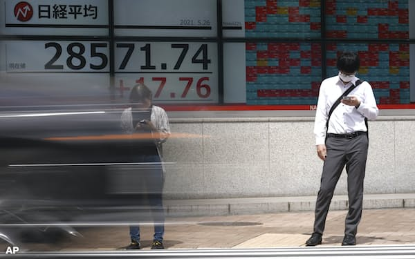 A man and a woman wearing protective masks stand in front of an electronic stock board showing Japan's Nikkei 225 index at a securities firm Wednesday, May 26, 2021, in Tokyo. Asian stock markets rose Wednesday as inflation fears eased and investors looked ahead to U.S. data that are expected to show economic growth accelerating. (AP Photo/Eugene Hoshiko)