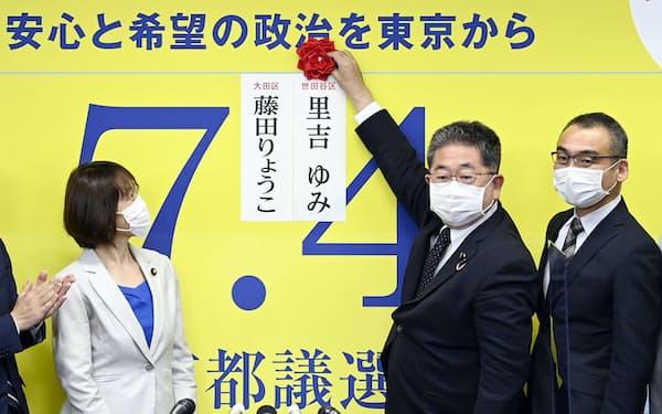 東京都議選で当選を決めた候補者の名前に花を付ける共産党の小池晃書記局長(右から2人目)4日夜、東京都渋谷区の党本部=共同