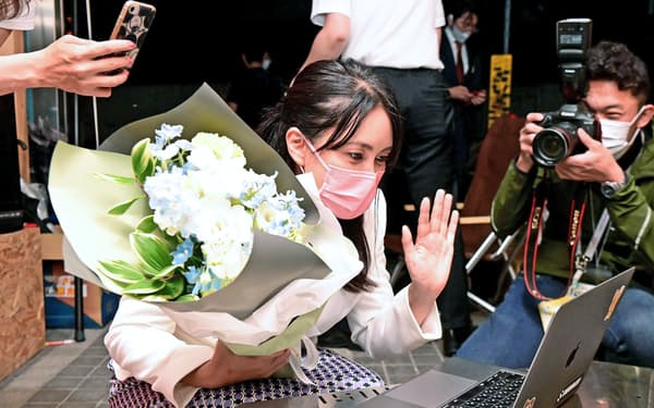 当選を決め、リモートでつないだ支援者らに手を振る都民ファーストの会の龍円愛梨氏(4日、東京・渋谷)