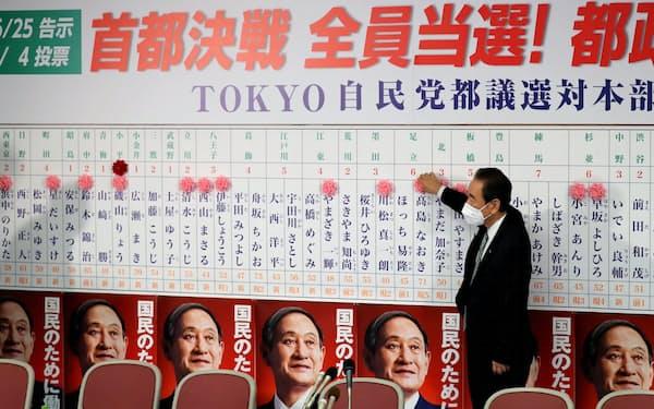 開票センターで当選のバラをつける自民党の鴨下都連会長(5日未明、自民党本部)