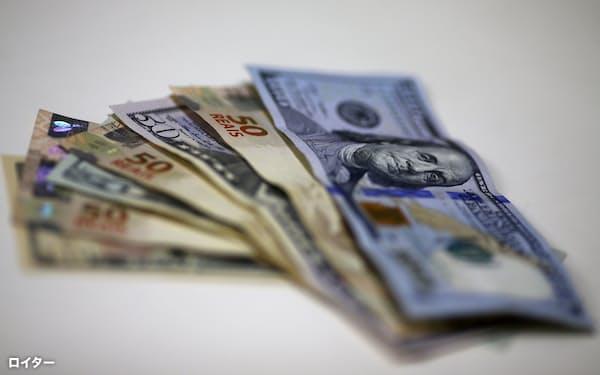 ブラジルレアルは資源高や中銀の利上げが追い風となった(ブラジル・リオデジャネイロの両替店の米ドルとブラジルレアル紙幣)=ロイター
