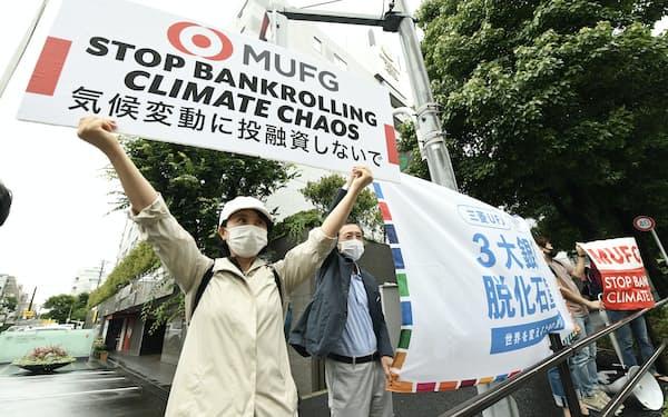 三菱UFJフィナンシャル・グループの株主総会会場前で環境対策を訴える人たち(6月29日午前、東京都港区)