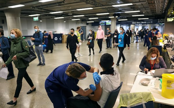 FILE PHOTO: A person receives a dose of the Pfizer BioNTech COVID-19 vaccine at a mass vaccination centre for those aged 18 and over at the Tottenham Hotspur Stadium, amid the coronavirus disease (COVID-19) pandemic, in London, Britain, June 20, 2021. REUTERS/Henry Nicholls/File Photo