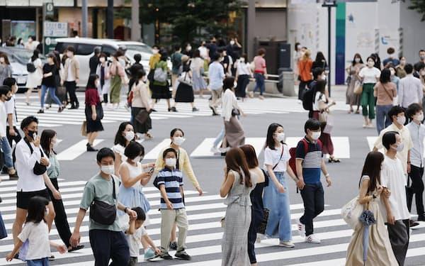 交差点を行き交う、マスク姿の人たち(6月、東京・銀座)=共同