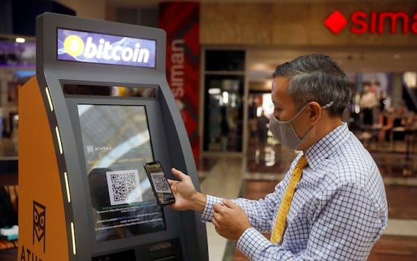 仮想通貨ATMの操作を説明するアテナビットコインの幹部(6月24日、サンサルバドル)=ロイター