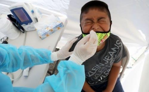 2020年7月、新型コロナの無料検査を受ける少年。米ロサンゼルス市サウスロサンゼルス地区のウォーカー・テンプルAME教会の外に設置された移動診療所にて。(PHOTOGRAPH BY MARIO TAMA, GETTY IMAGES)