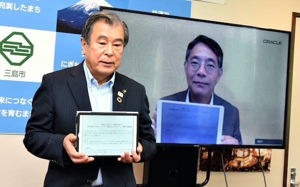 協定を締結した三島市の豊岡武士市長(左)と日本オラクルの三沢智光社長(画面内)