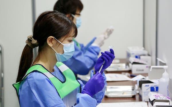 大阪府コロナワクチン接種センターで注射器にワクチンを充填する看護師(大阪市中央区のマイドームおおさか)