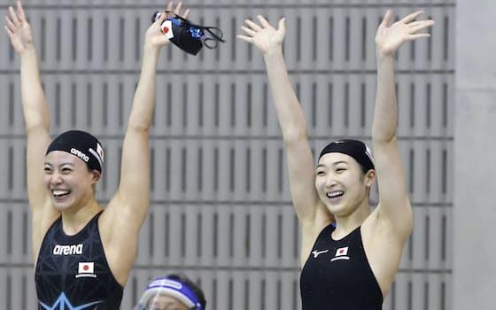 日本新を更新し、両手を挙げて喜ぶ池江(右)と大本(4日)=共同