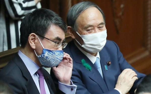 衆院本会議場で菅首相(右)と言葉を交わす河野規制改革相(4月)