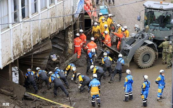 土石流の被災現場で捜索活動する警察官や消防隊員ら(6日、静岡県熱海市伊豆山)=共同