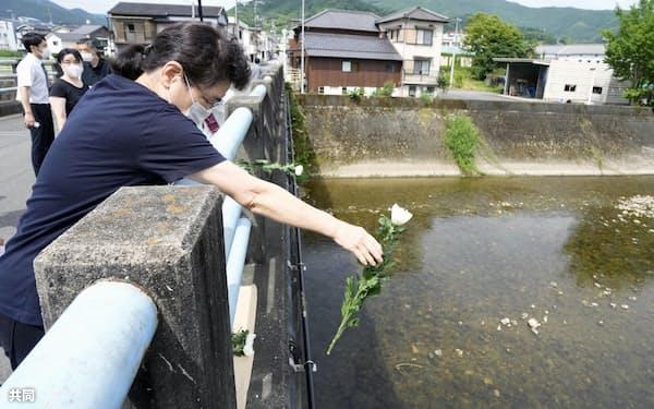 西日本豪雨から3年となり、川に花を手向ける女性(7日午前、愛媛県西予市)=共同