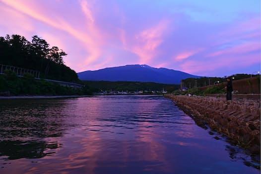 吹浦川河口から望む夕暮れの鳥海山。つかの間、空と川面がバラ色に染まった