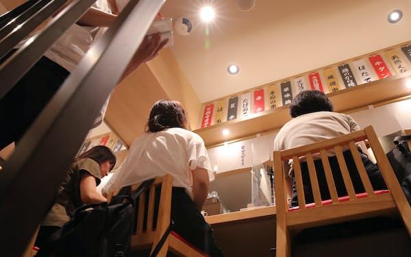パーテーションで区切られたカウンター席で飲食する人たち(8日、大阪市中央区)