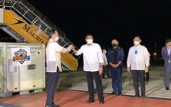 ワクチンが到着し、こぶしを合わせて挨拶する中田昌宏公使(左)とドゥテルテ大統領(マニラ首都圏)=在フィリピン日本大使館提供