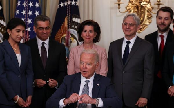 9日、関係省庁の閣僚らの前で大統領令に署名するバイデン氏(中央下、ホワイトハウス)=ロイター