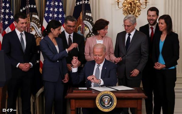 大統領令に署名後、ペンをリナ・カーンFTC委員長(左から2番目)に手渡すバイデン大統領(9日、ホワイトハウス)=ロイター