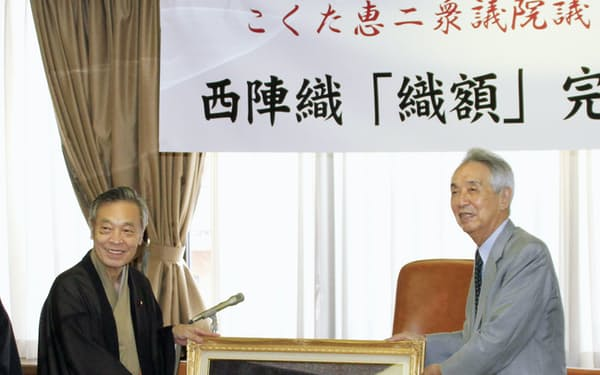 国会に掲示する肖像画を披露する共産党の穀田恵二国対委員長。右は伊吹文明元衆院議長(10日午後、京都市上京区)=共同