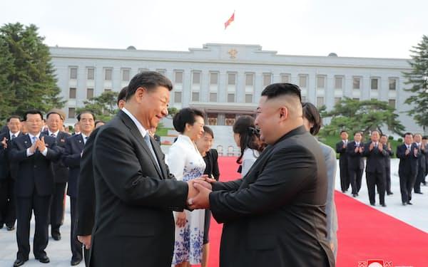 朝鮮労働党本部を訪れた習近平氏(手前左)と握手する金正恩氏(2019年6月、平壌)=朝鮮中央通信・共同