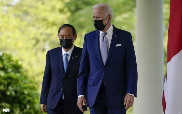 共同記者会見に向かうバイデン米大統領(右)と菅首相(4月、ワシントンのホワイトハウス)=AP・共同