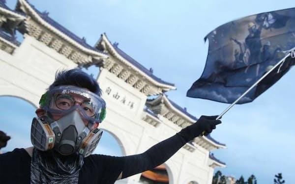 香港の民主化を求めて台北で行われた集会で旗を振る香港人の参加者=AP