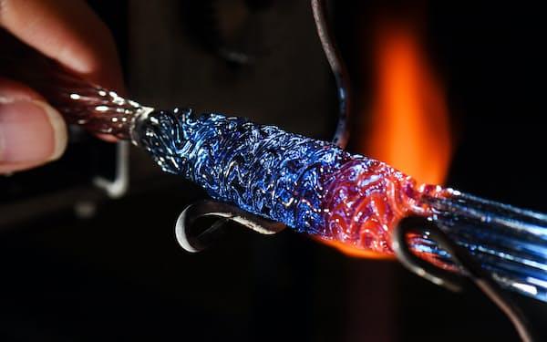 バーナーの炎で硬質ガラスを溶かして、ひねりながら模様を作る(京都市左京区)=目良友樹撮影