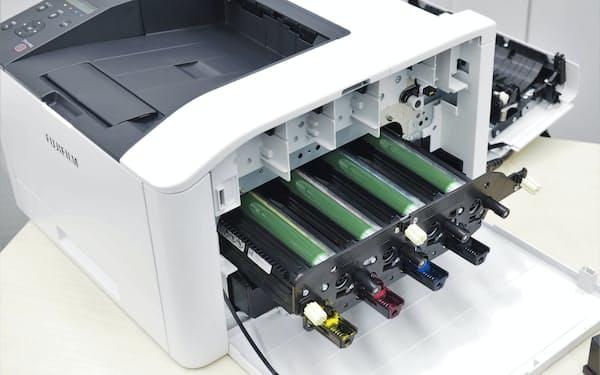 ApeosPrint C320 dwの外装の一部を外した状態。4本並んでいる緑色の筒状の部品が、用紙にトナーを転写するために欠かせない「感光体」(出所:日経クロステック)