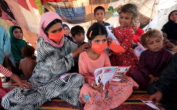 少女に国連児童基金(ユニセフ)から配られたマスクを付ける女性(アフガニスタン東部のキャンプで、2020年6月)=ロイター
