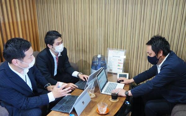 二人三脚でITサービスの導入を進める大倉商店の大倉社長(右)と伊予銀行員(左)