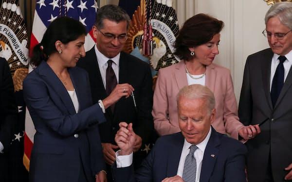 大統領令に署名後、大企業の市場支配に批判的なリナ・カーンFTC委員長(左)にペンを手渡すバイデン大統領=ロイター