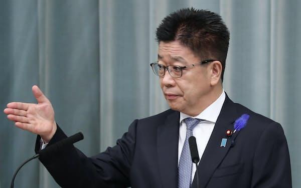 記者会見する加藤官房長官(13日、首相官邸)