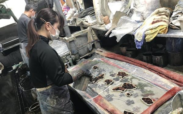 ノリが塗られた綿布の束の上から壺人が柄に合わせて染料を注ぎ、下から圧縮空気で吸い込むことで一気に染め上げる(堺市の協和染晒工場で)