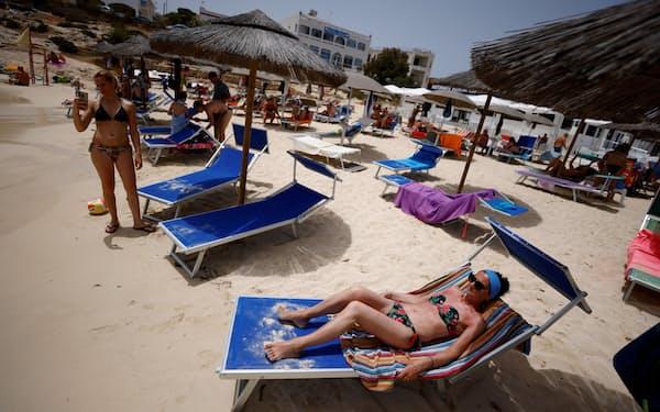 地中海の島のビーチでくつろぐ観光客ら(6月、イタリア)=ロイター