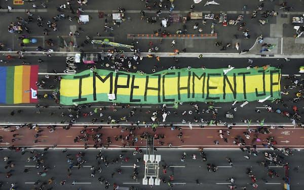 ボルソナロ大統領の弾劾を求める横断幕。有権者の54%が同氏の解職を支持している=AP